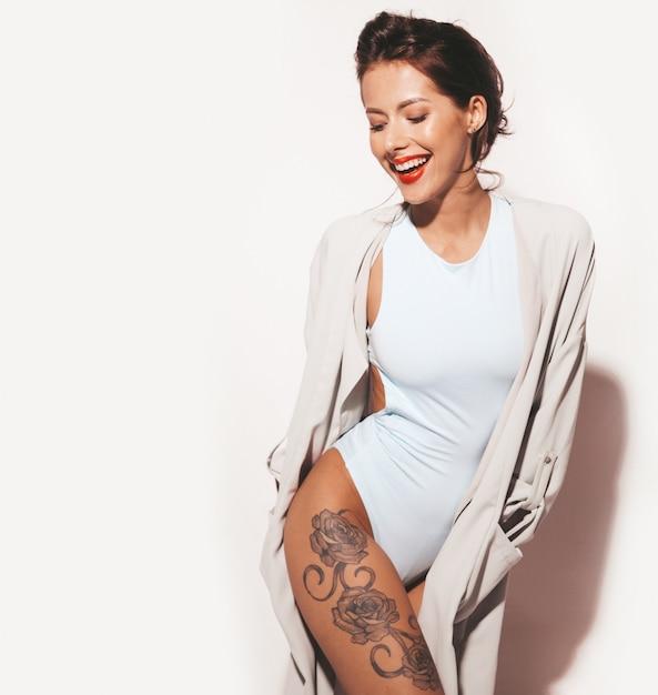 Portret van mooie sexy lachende brunette vrouw. het meisje kleedde zich in toevallige lingerie van het de zomer blauwe lichaam. model op witte achtergrond wordt geïsoleerd die Gratis Foto