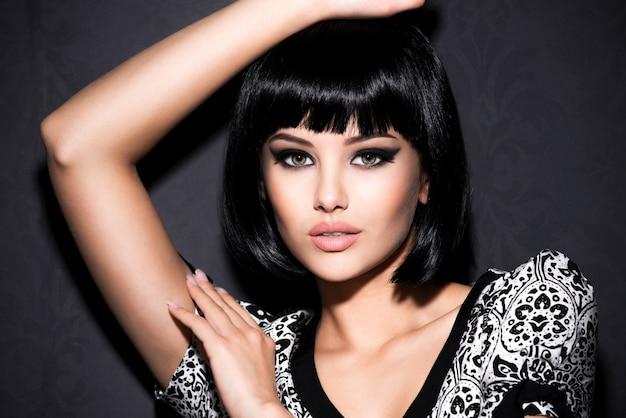Portret van mooie sexy vrouw met lichte make-up die zich voordeed op een grijze achtergrond Gratis Foto