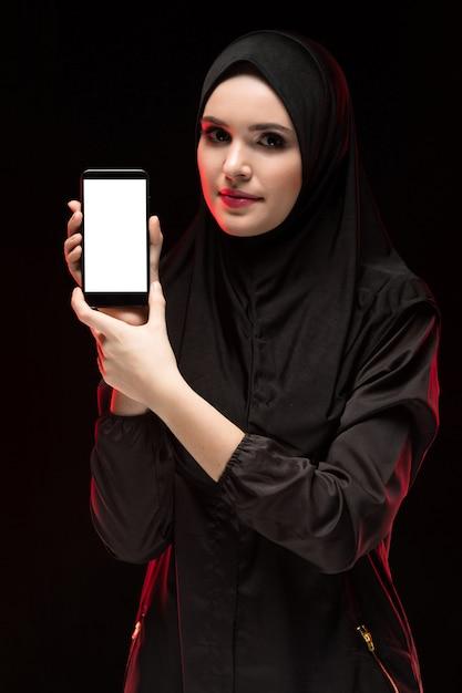 Portret van mooie slimme jonge moslimvrouw die zwarte hijab dragen die mobiele telefoon in haar handen adverteren als zwarte van het onderwijsconcept Premium Foto