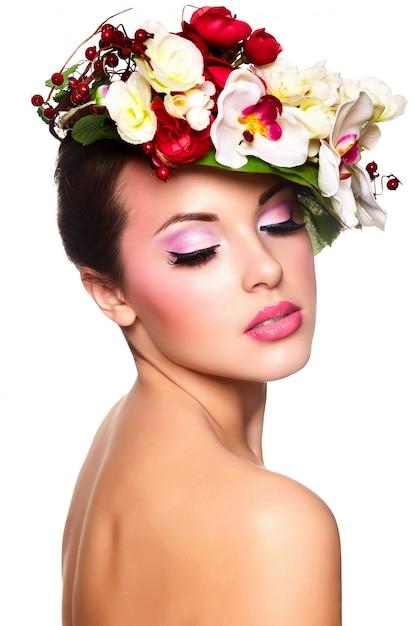 Portret van mooie stijlvolle jonge vrouw met kleurrijke bloemen op hoofd Gratis Foto