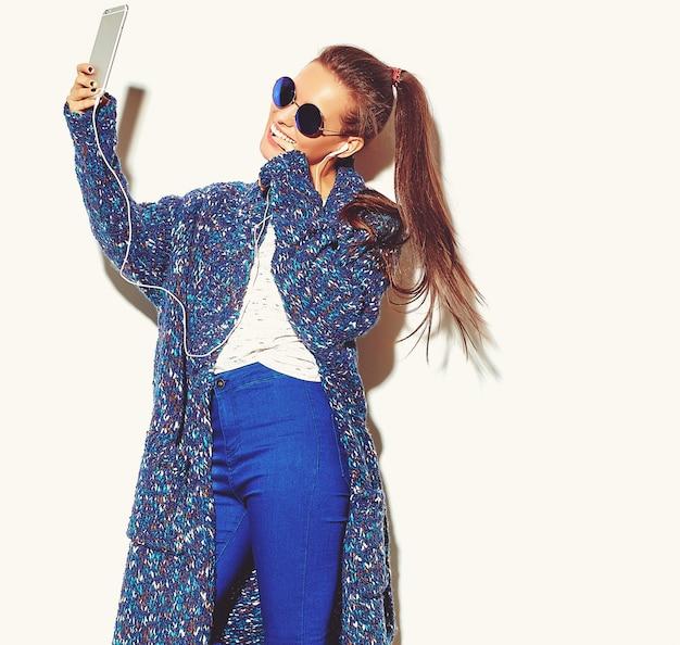 Portret van mooie stijlvolle jonge vrouw met oortelefoons Gratis Foto