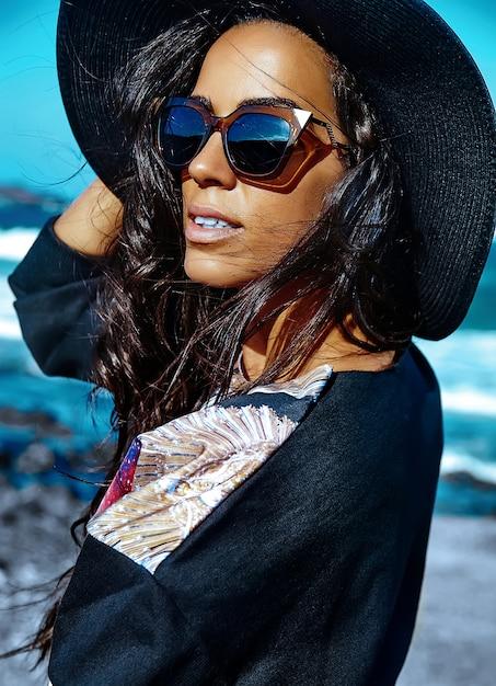 Portret van mooie stijlvolle jonge vrouw op het strand Gratis Foto