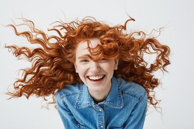 Portret van mooie vrolijke roodharige vrouw met vliegende krullend haar lachend lachen. Gratis Foto