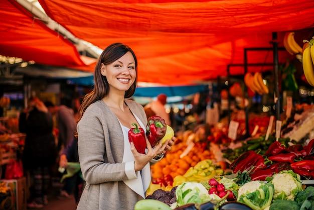 Portret van mooie vrouw bij landbouwersmarkt het kopen paprika. Premium Foto