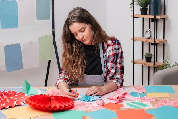 Portret van mooie vrouw die het creatieve werk van de origamikunst maakt Gratis Foto