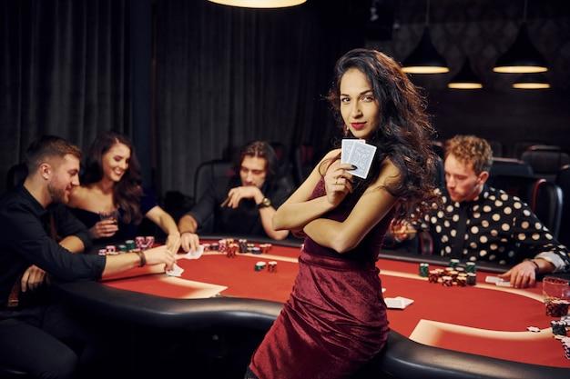 Portret van mooie vrouw. groep elegante jongeren die samen pokeren in casino Premium Foto