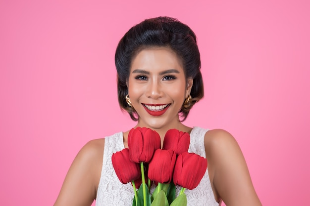 Portret van mooie vrouw met boeket van rode tulpenbloemen Gratis Foto