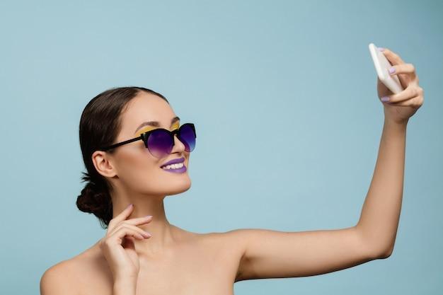 Portret van mooie vrouw met lichte make-up en zonnebril op blauwe studioachtergrond. stijlvol en modieus merk en kapsel. kleuren van de zomer. schoonheid, mode en advertentieconcept. selfie maken. Gratis Foto