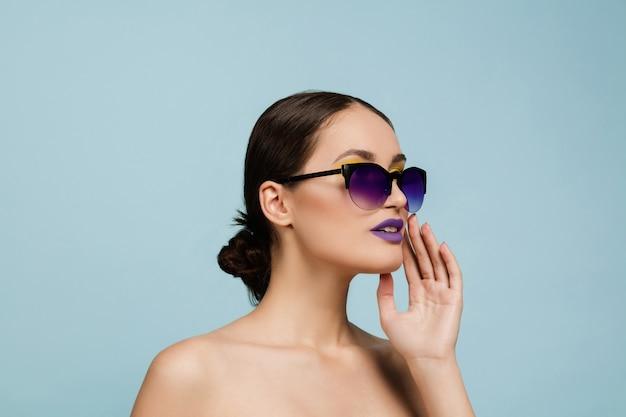 Portret van mooie vrouw met lichte make-up en zonnebril op blauwe studioachtergrond. stijlvol, modieus merk en kapsel. kleuren van de zomer. schoonheid, mode en advertentieconcept. iemand bellen. Gratis Foto