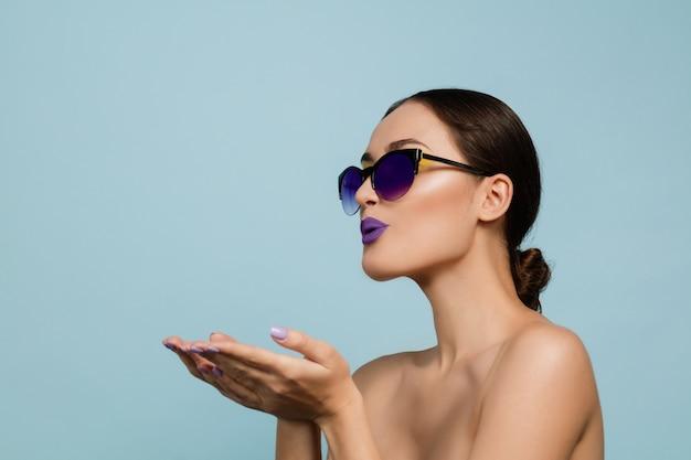 Portret van mooie vrouw met lichte make-up en zonnebril op blauwe studioachtergrond. stijlvol, modieus merk en kapsel. kleuren van de zomer. schoonheid, mode en advertentieconcept. kusjes sturen. Gratis Foto