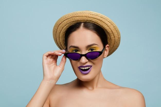 Portret van mooie vrouw met lichte make-up, hoed en zonnebril op blauwe studioachtergrond. stijlvol en modieus merk en kapsel. kleuren van de zomer. schoonheid, advertentieconcept. zoekt brillen op. Gratis Foto