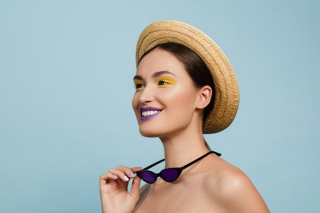 Portret van mooie vrouw met lichte make-up, hoed en zonnebril op blauwe studioachtergrond. stijlvol en modieus merk en kapsel. kleuren van de zomer. schoonheid, mode, advertentieconcept. kijkt naar de zijkant. Gratis Foto