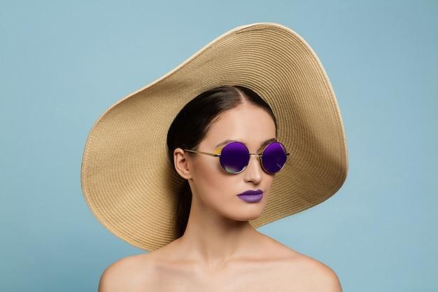 Portret van mooie vrouw met lichte make-up, hoed en zonnebril op blauwe studioachtergrond. stijlvol en modieus merk en kapsel. kleuren van de zomer. schoonheid, mode en advertentieconcept. echt. Gratis Foto