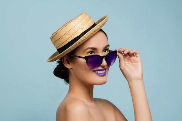 Portret van mooie vrouw met lichte make-up, hoed en zonnebril op blauwe studioachtergrond. stijlvol en modieus merk en kapsel. kleuren van de zomer. schoonheid, mode en advertentieconcept. retro. Gratis Foto