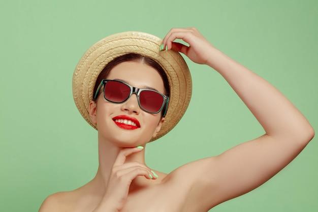 Portret van mooie vrouw met lichte make-up, hoed en zonnebril op groene ruimte. stijlvol en modieus merk en kapsel. kleuren van de zomer Gratis Foto
