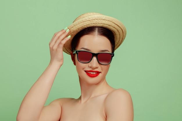 Portret van mooie vrouw met lichte make-up, hoed en zonnebril op groene studioachtergrond. stijlvol en modieus merk en kapsel. kleuren van de zomer. schoonheid, mode en advertentieconcept. lachend. Gratis Foto