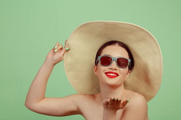 Portret van mooie vrouw met lichte make-up, rode brillen en hoed op groene ruimte. stijlvol en modieus merk, kapsel. schoonheid, mode en advertentieconcept Gratis Foto