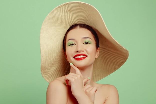 Portret van mooie vrouw met lichte samenstelling en hoed op groene ruimte. stijlvol en modieus merk en kapsel. kleuren van de zomer Gratis Foto