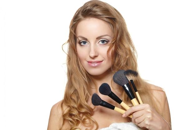 Portret van mooie vrouw met make-upborstels Gratis Foto