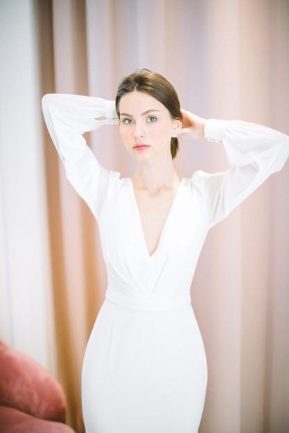 Portret van mooie vrouw op parel kamer permanent en houdt haar haren in lange witte jurk Gratis Foto