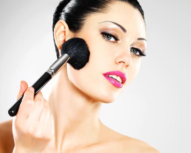 Portret van mooie vrouw rouge toe te passen op gezicht met behulp van cosmetische borstel Gratis Foto