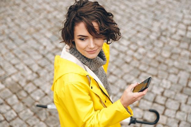 Portret van mooie vrouwelijke jaren '20 die op straatstenen met mobiele telefoon en paraplu in handen lopen die naar juiste route zoeken Gratis Foto