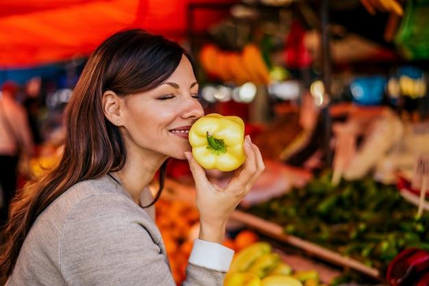 Portret van mooie vrouwen ruikende paprika bij markt. de geur van verse groente is geweldig Premium Foto