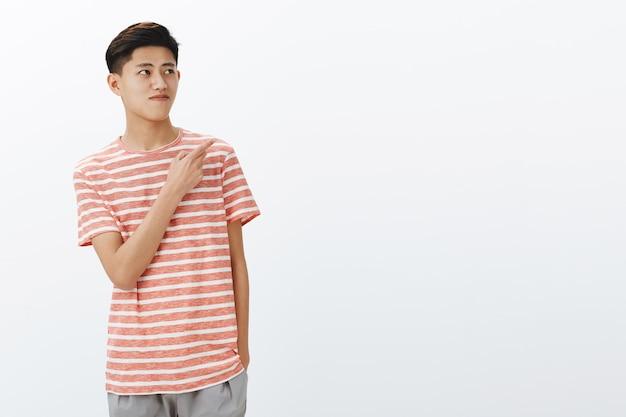 Portret van nieuwsgierig aardig jong aziatisch mannelijk model in gestreept t-shirt staande ontspannen over grijze muur met hand in zak kijkend en wijzend naar de rechterbovenhoek zien interessante kopie ruimte Gratis Foto