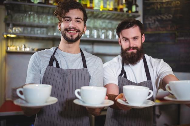 Portret van obers waar een kopje koffie bij teller Gratis Foto