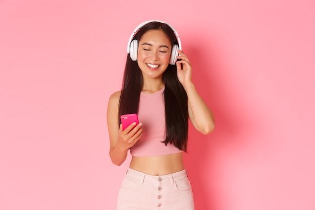 Portret van onbezorgde aantrekkelijke aziatische vrouw die van favoriet lied geniet, ogen dicht om te ontspannen terwijl het luisteren naar muziek in hoortelefoons, mobiele telefoon vasthoudt en zich over roze achtergrond bevindt. Gratis Foto