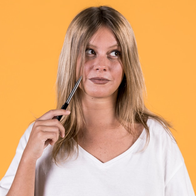 Portret van onbruikbare nadenkende jonge vrouw voor gele achtergrond Gratis Foto
