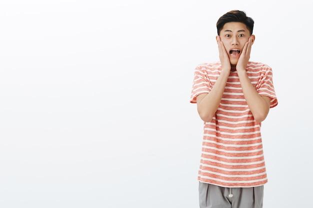 Portret van onder de indruk en verrast opgewonden jonge aziatische mannelijke student die schreeuwt van verbazing en vreugde handen tegen wangen drukt en opgewonden en verbaasd staart aan de rechterkant van de kopie ruimte Gratis Foto