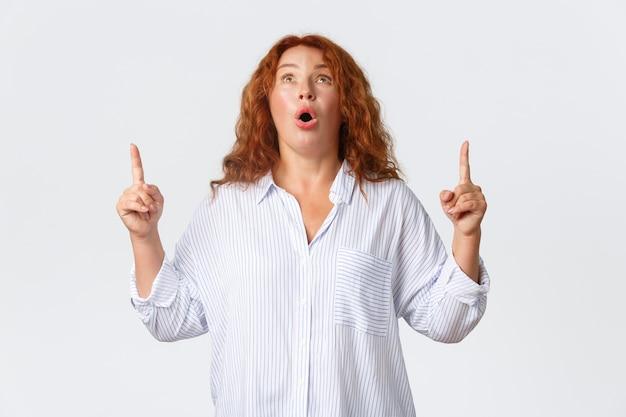 Portret van onder de indruk hijgende roodharige vrouw hijgend verbaasd, open mond gefascineerd, zeggend wow, kijkend en wijzend vingers omhoog naar superaanbieding, met banner met advertentie. Gratis Foto