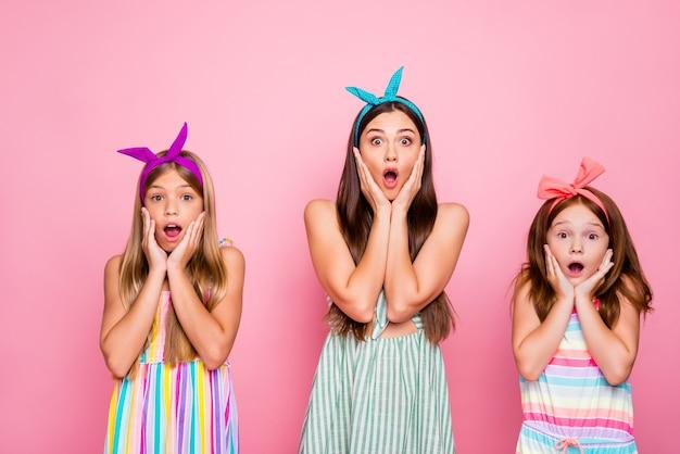 Portret van onder de indruk meisjes met kleur hoofdbanden die omg schreeuwen hun wangen aanraken nieuws horen dragen jurk rok geïsoleerd op roze achtergrond Premium Foto