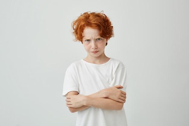 Portret van ongelukkige roodharige jongen met sproeten op zoek met verstoorde uitdrukking, gekruiste handen ontevreden dat zijn moeder hem uitschold. Gratis Foto