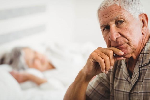 Portret van ongerust gemaakte hogere mensenzitting op bed in slaapkamer Premium Foto