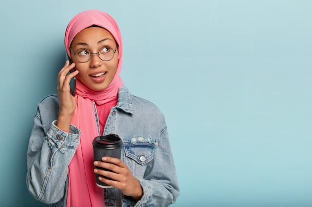 Portret van opgetogen arabische vrouw maakt regeling via mobiele telefoon, houdt papieren kopje koffie, ontvangt goed aanbod, kijkt opzij Gratis Foto