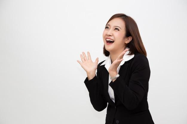 Portret van opgewekte gillende jonge aziatische onderneemster die zich in bedrijfs formeel kostuum bevinden dat over wit wordt geïsoleerd Premium Foto