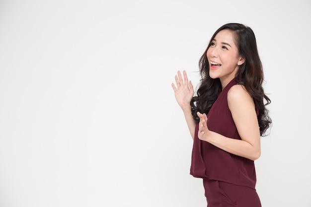 Portret van opgewekte gillende jonge aziatische vrouw die zich in rode kleding bevindt die op wit wordt geïsoleerd Premium Foto