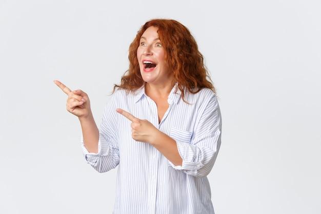 Portret van opgewonden en verbaasde, gelukkige vrouw van middelbare leeftijd reageert op een spannende promobanner, wijst en kijkt gefascineerd in de linkerbovenhoek, opgewekt over een witte achtergrond. Gratis Foto