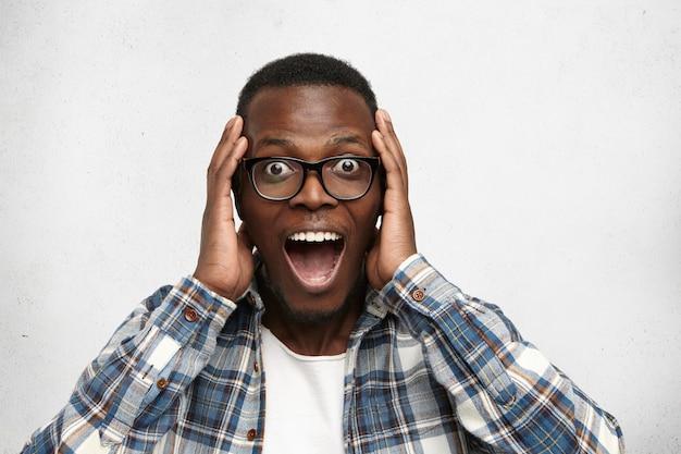 Portret van opgewonden jonge afro-amerikaanse man schreeuwen in shock en verbazing hand in hand op het hoofd. verraste zwarte hipster met grote ogen die onder de indruk is, kan zijn eigen geluk en succes niet geloven Gratis Foto