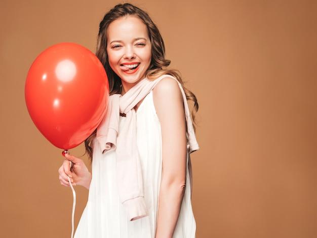 Portret van opgewonden jonge meisje poseren in trendy zomer witte jurk. glimlachende vrouw met het rode ballon stellen. model klaar voor feest Gratis Foto