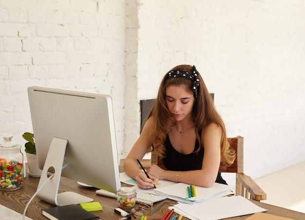 Portret van opmerkzame jonge vrouw die vreemde talen op internetwebsite studeert en notities op stickers maakt om nieuwe woorden beter te onthouden. kopieer de ruimtemuur voor reclame-inhoud of tekst. Gratis Foto