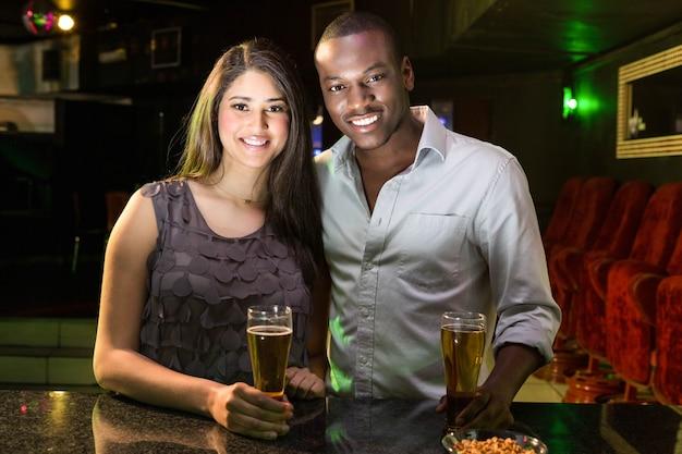 Portret van paar die bier hebben bij barteller in bar Premium Foto