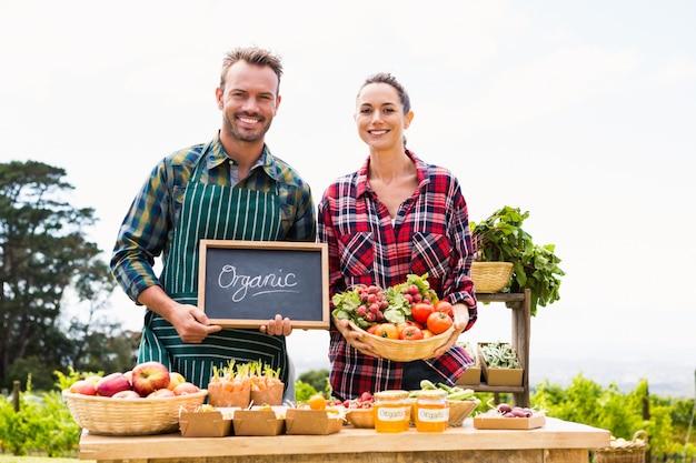 Portret van paar met bord en mand verkopende groenten Premium Foto