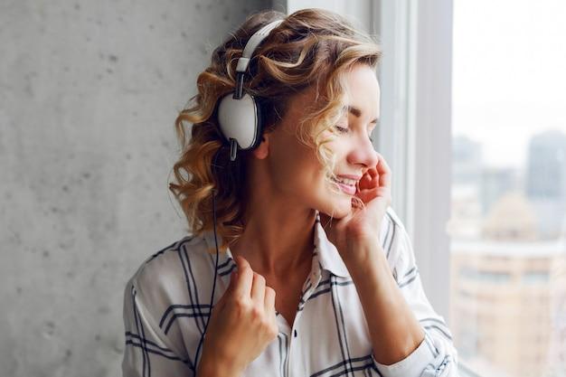 Portret van peinzende lachende vrouw luisteren muziek door oortelefoons, poseren in de buurt van venster close-up. modern stedelijk interieur. Gratis Foto