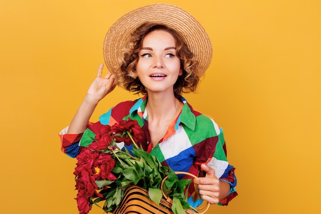 Portret van peinzende vrouw met krullend kapsel met boeket van pionen in handen close-up. gele muur achtergrond. Gratis Foto