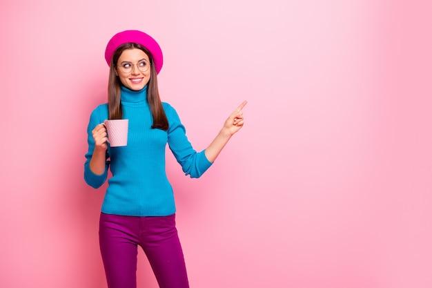 Portret van positief frans meisje reizen trip punt wijsvinger kopie ruimte toon café cafetaria verkoopbevordering houd cup latte advertenties dragen blauwe broek. Premium Foto