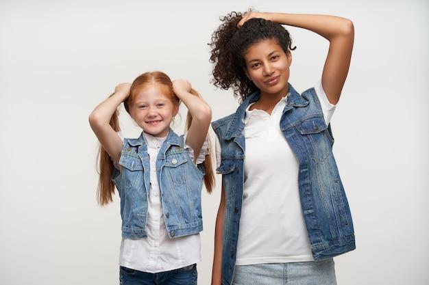 Portret van positieve jonge dames in jeansvesten en witte shirts die hun lange haar met opgeheven handen met lichte glimlach, geïsoleerd op wit houden Gratis Foto