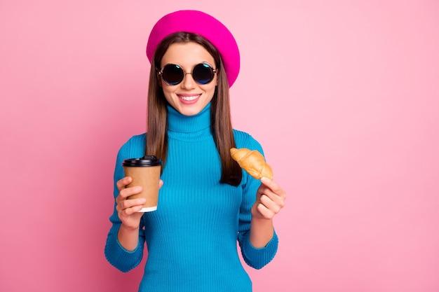 Portret van positieve meisje reizen cafetaria ontspannen cafetaria houden afhaalmaaltijden mok espresso drank lekker croissant dragen blauwe trui zonnebril hoofddeksels. Premium Foto